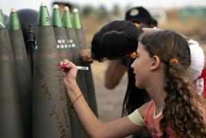 Israeli girls write messages in Hebrew on shells ready to be fired toward Hezbollah targets in southern Lebanon. Photo: AFP